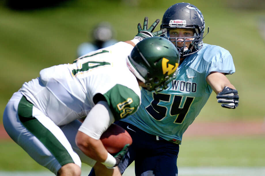 NICK KING | nking@mdn.net  Northwood's Michael Fisher, left, tackles Wayne State quarterback Donovan Zezula in the season-opening game in Midland. Fisher, who plays middle linebacker, soon should become the program's all-time leading tackler. / Midland Daily News