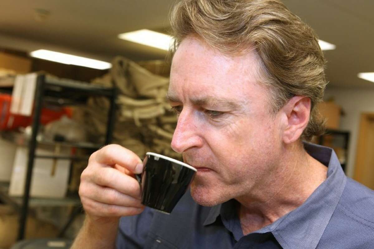 Richard Colt smells the aroma of a sample of coffee at Java Pura Coffee Roasters.