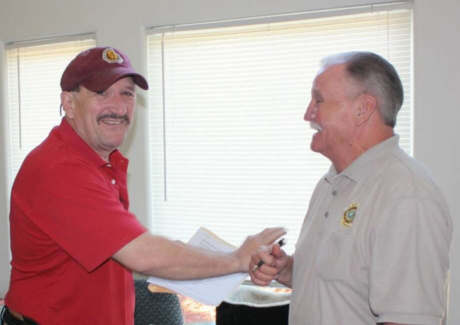 San Jacinto County Pct. 3 Justice of the Peace Randy Ellisor (left) and Pct. 1 Constable Roy Rogers share a few laughs before beginning instruction for the concealed handgun class held at Ellisor's home on June 29.