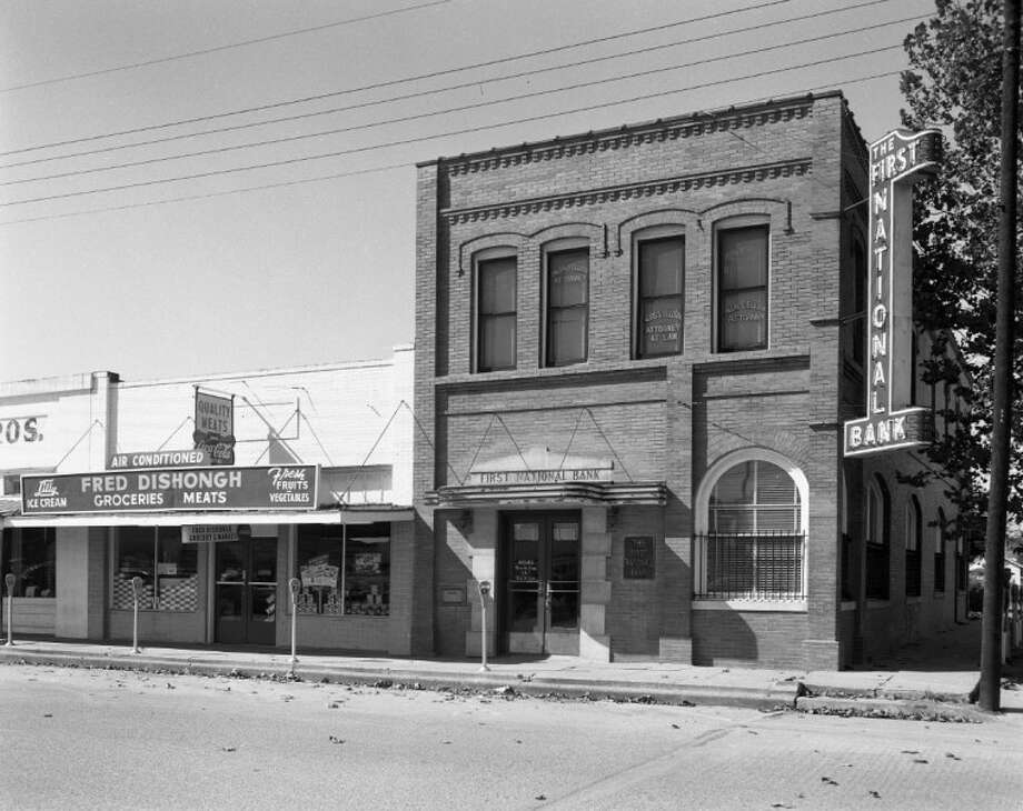 The First National Bank and Dishongh Grocery were located in the 100 block of N. San Jacinto St. The bank is now the Prosperity Bank and is located across the street from this location. Both buildings recently housed the Second Chance resale shop. Notice the air conditioned sign on the store and the parking meters out front. Alvis Ellisor had his law office upstairs in the bank building. Photo: MOON YOUNG