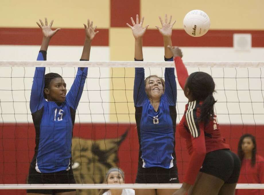 Cypress Creek's Dani Fielder and Lauren Aschbacher attempt to block a spike from Cypress Woods' Olivia Ogwumike at Cypress Woods High School on Wednesday. Photo: Karl Anderson