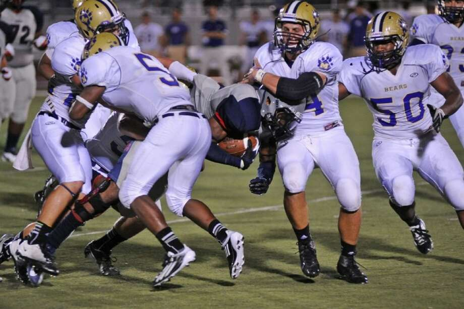 Montgomery defenders Herbert House (5), Trace Mock and Jaylin Hemphil-Poplar (50) converge on Dawson's Jared Garcia during last week's game.