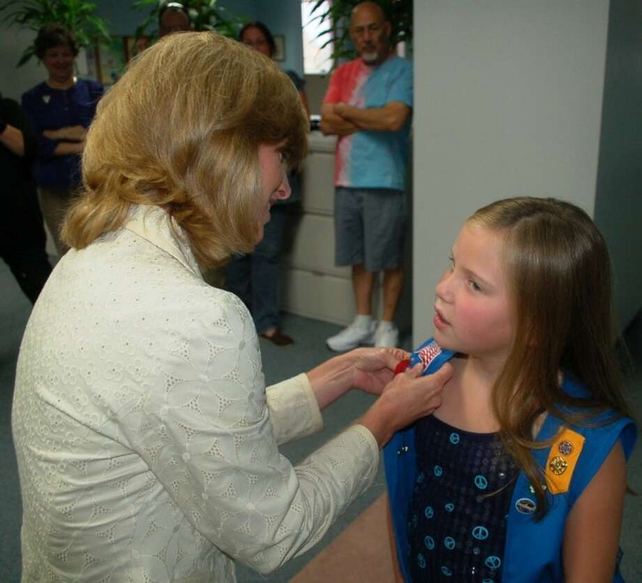 Maggie Miksch, 7, receives her Girl Scout Medal of Honor from Girl Scouts of San Jacinto Council CEO Mary Vitek. Maggie earned the award for saving the life of her grandfather. These awards recognize Girl Scouts from 5-17 years of age who have heroically saved or attempted to save a life. Maggie is only one of 13 girls in the nation to receive this prestigious award this year. Photo: Submitted Photo