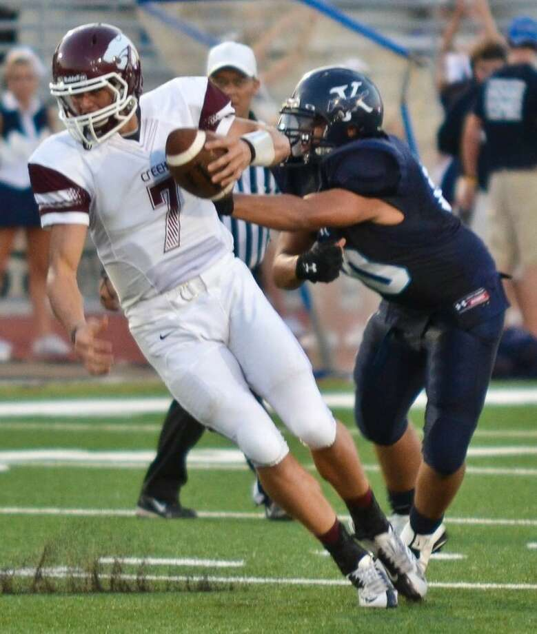 Clear Creek quarterback Jarrett Hildreth eludes the grasp of Kingwood lineman Thomas Smitherman in the first quarter of the Wildcats' 34-14 win over the Mustangs Sept. 7. Hildreth eventually gained seven yards on the play. Photo: Photo By Stephen Whitfield