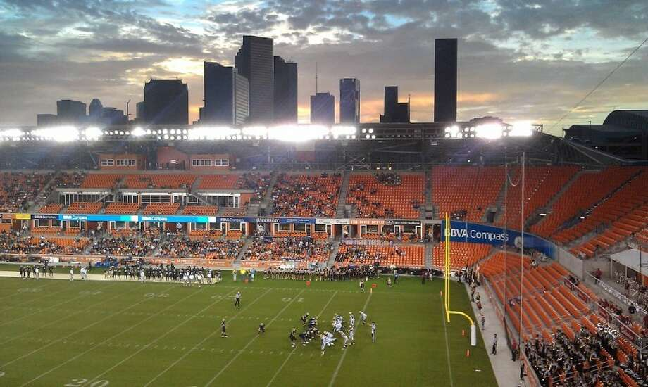 Thoughts: Just a nice setting the scene image. The viewer gets a good idea where the game being played.Caption: Cy Woods and Klein Collins face off as the sun sets on the Houston skyline during a high school football game at BBVA Compass Stadium, Saturday, Sept. 1, 2012. Photo: Jason Fochtman
