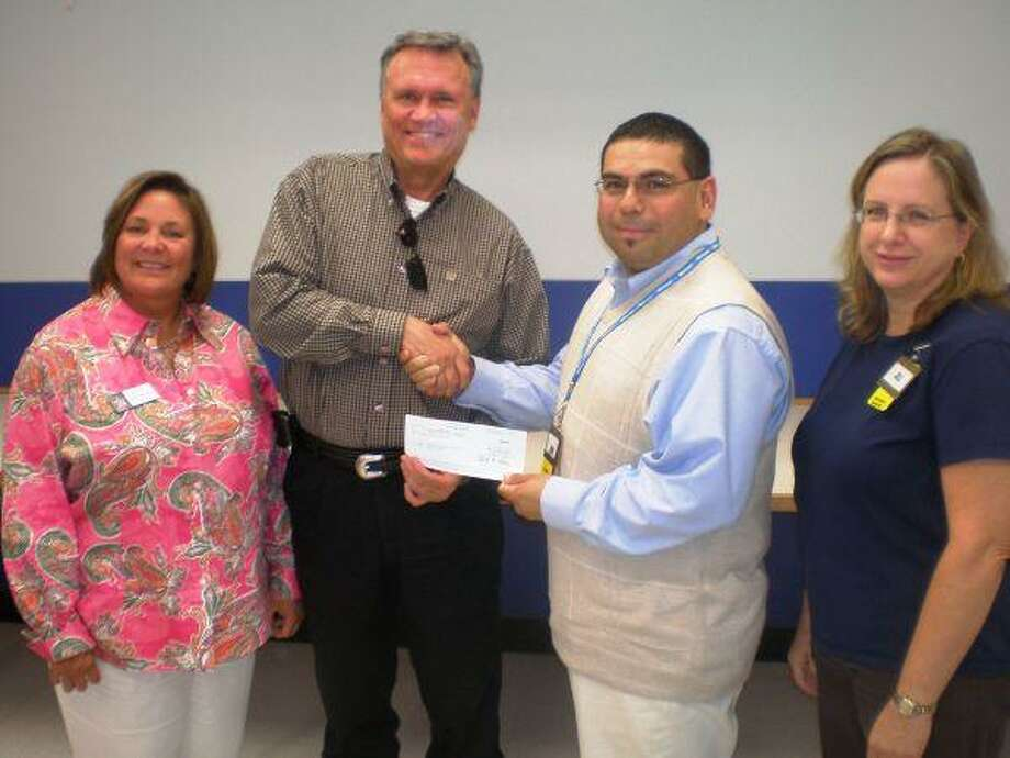 """Northeast Hospital Foundation President Norman Funderburk, second from left, accepts a donation from Mike Manyose, shift manager, and Jill Adams, right, personnel manager with the Atascocita Walmart. Pictured with them is Devon Alexander, co-chair of the foundation's """"In the Pink of Health"""" Host Committee. The Atascocita Walmart has joined with the Humble and Fall Creek Walmarts to support the foundation's annual """"In the Pink of Health"""" luncheon which will benefit the cancer program at Memorial Hermann Northeast Hospital. The annual luncheon will be held Friday, Oct. 15, at the Houston Airport Marriott Hotel and will feature actress, comedian and breast cancer survivor Marcia Wallace. For more information about the luncheon, go to www.northeasthospitalfoundation.org."""