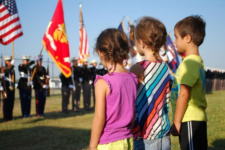 Twins Lincoln and Riley Ferrante, 5, right, and sister Lola, 4, listen to the national anthem before Houston's inaugural 9/11 Heroes Run in Sept. 2011 at Ellington Airport. The siblings had recently moved to Houston, where their dad, who ran in the 5K, is stationed in the Coast Guard.