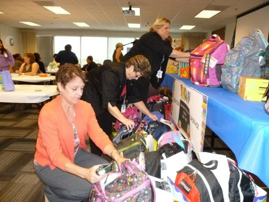 Kim Hennessy, LaPorte resident Bonnie Hebert and Kelly Sherbert (left to right) of the Harris County Appraisal District's Information and Assistance division fill 34 backpacks with school supplies donated by other HCAD employees before delivering them to the YMCA's Operation Backpack school supply drive.
