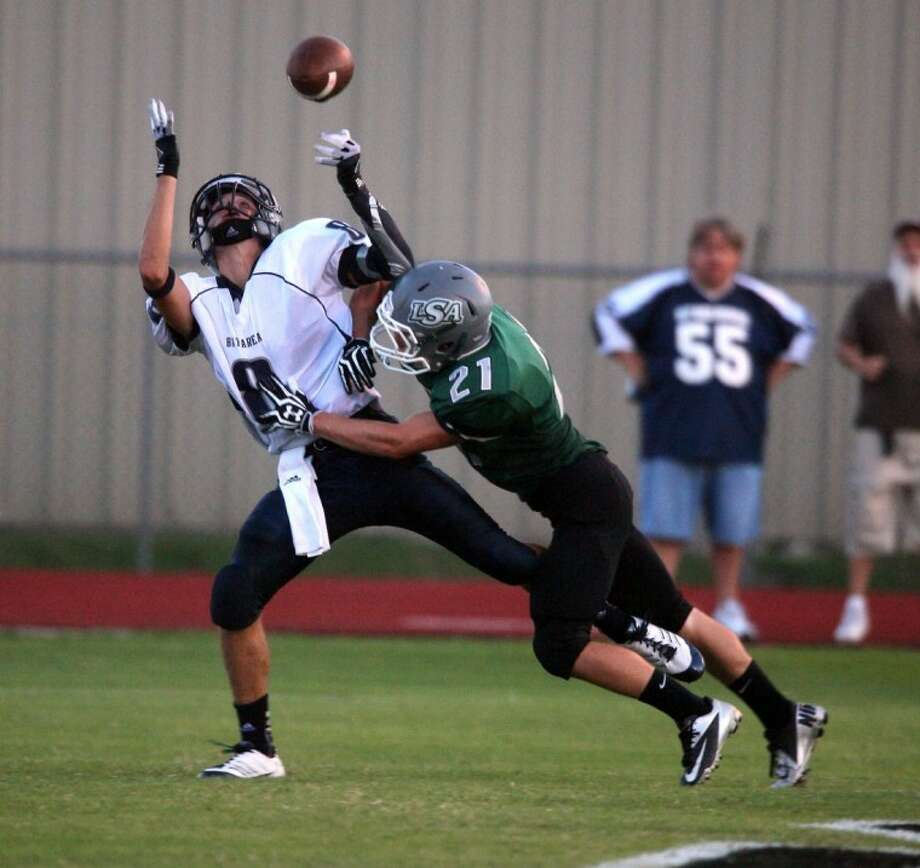 Bay Area Christian's Garrett Gleaton-Marcantel (8) is hit by Lutheran South Academy's Tyler Trochesset just prior to the ball arriving in the team's game last Friday. LSA rallied for a 20-17 win. Photo: KAR HLAVA