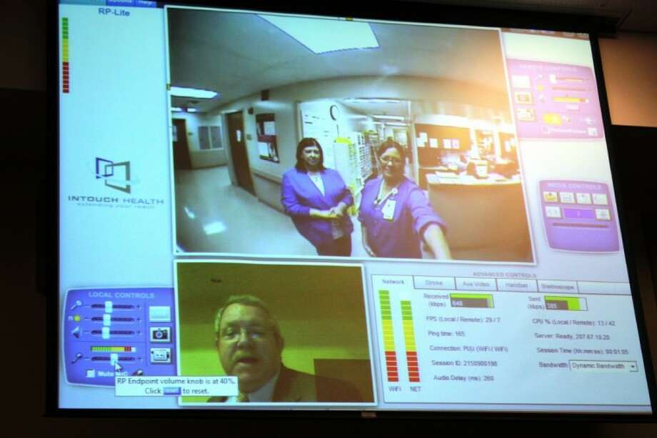 Pat Leahy of Intouch Health regional account manager, bottom, spoke to nurses Beckey Lindsey, left and Lisa Paxton, right, at the Cleveland Regional Medical Center via computer during a live demonstration of telemedicine technology at the Greater Cleveland Chamber of Commerce luncheon held on Sept. 6. The technology is used by doctors at Memorial Hermann in the Texas Medical Center to diagnose patients in Cleveland. Photo: MELECIO FRANCO