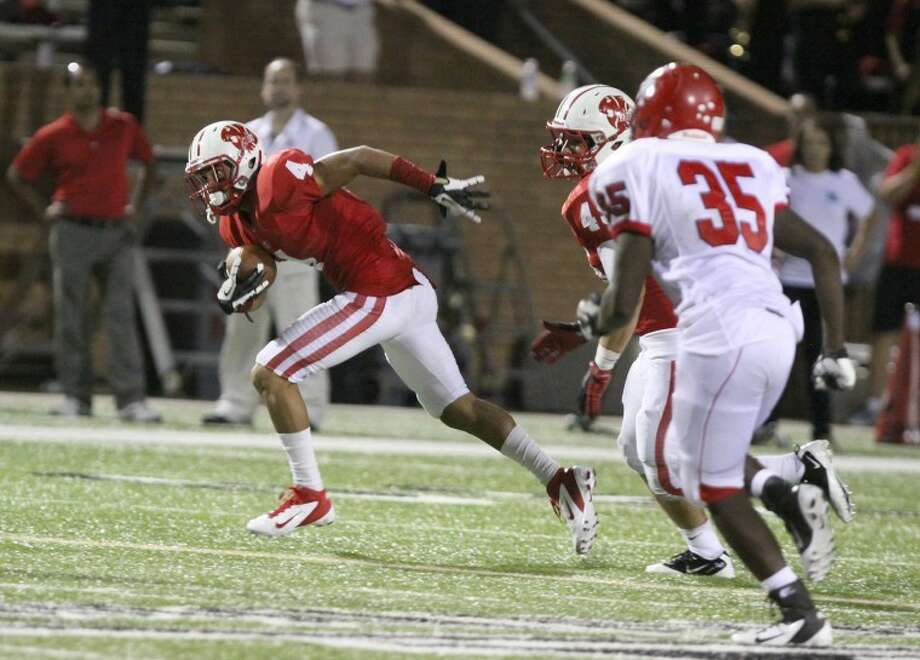 Katy's Isaiah Brown runs back an interception against Alief Taylor on Friday, one of two picks for Brown including one for a first-quarter touchdown. Photo: Alan Warren/HCN