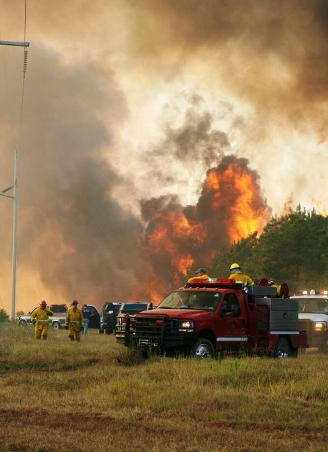 Firefighters scramble to get out of the way of a woods fire on FM 943 near Segno. Around 5:30 p.m. Sunday, the fire began moving quickly in a stand of trees near a Sam Houston EC power plant near Menard Chapel Road. It was feared the fire would jump the road and continue moving south, but firefighters were able to contain it. Photo: VANESA BRASHIER