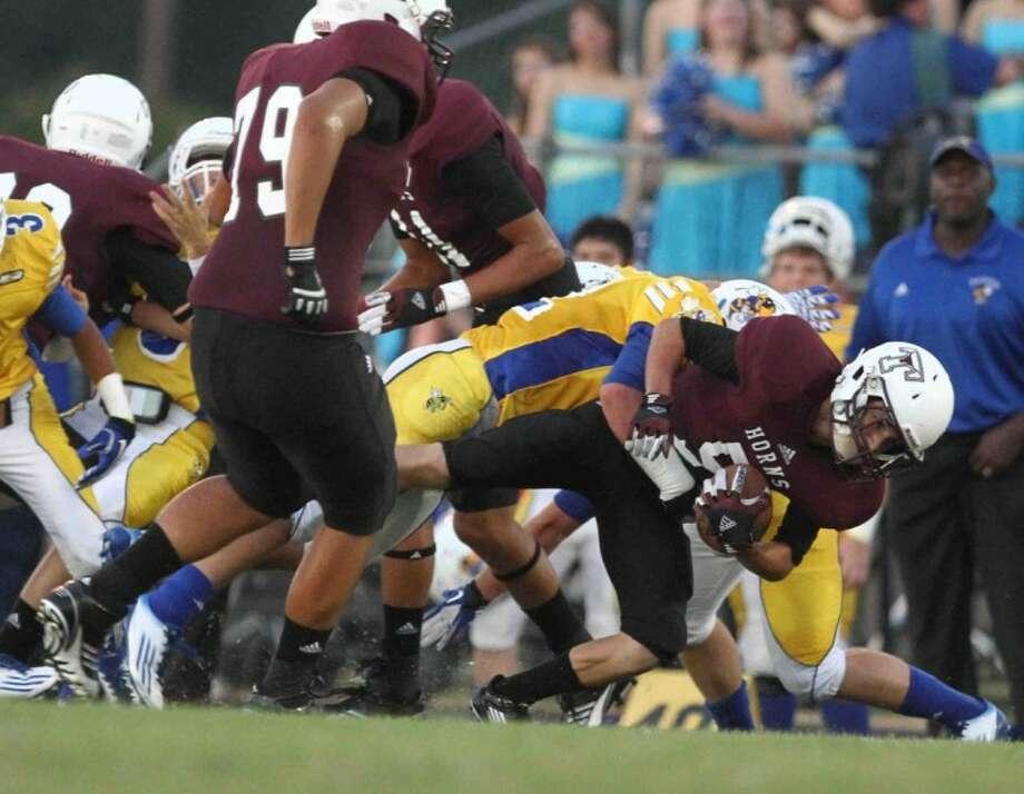Tarkington running back Larame Nash (5) is taken down during a high school football game in Tarkington on Sept. 7. Tarkington defeated Hardin 20-19.