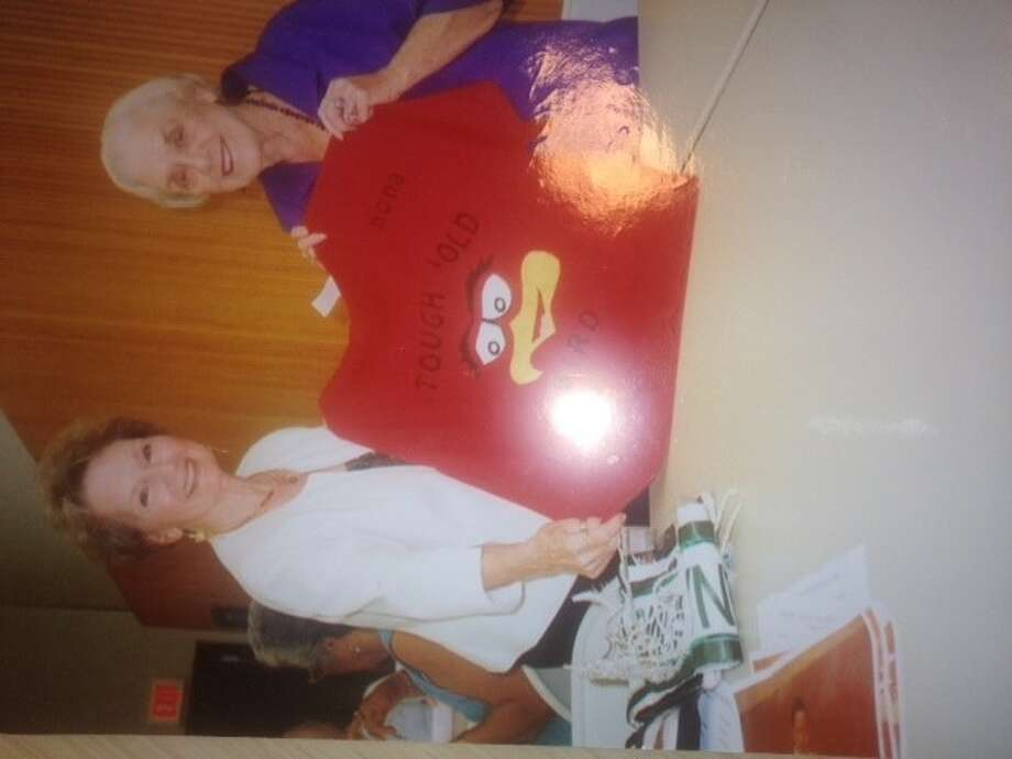 """Ann Cunningham (left) presents Nona Phillips with a t-shirt that reads """"Nona is a tough old bird."""" Phillips was recently released from the hospital after a long illness."""