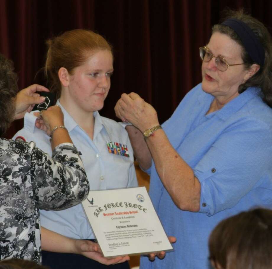 Coldspring-Oakhurst junior Christine Anderson's grandmothers, Karen Robertson and Alice Goodman, right, attach her new shoulder boards during the Pinning-On Ceremony at the Third Annual Air Force JROTC Welcome Back Social. Photo: CASSIE GREGORY