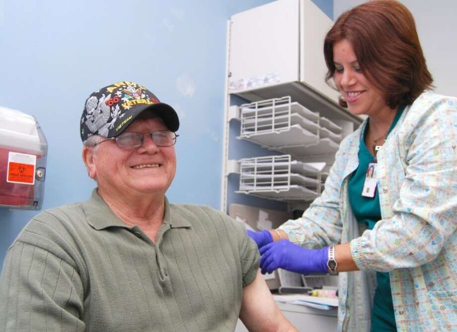 Prime care nurse Zulines Del Toro, gives U.S. Army veteran James Schultz his flu shot.