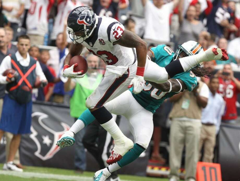 Houston Texans running back Arian Foster jumps over the goal line and Miami Dolphins safety Chris Clemons to score at Reliant Stadium in Houston. Photo: Alan Warren/HCN