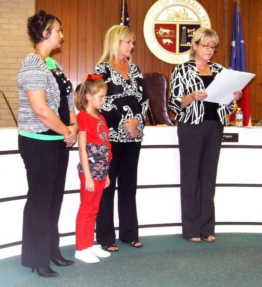 Tomball Mayor Gretchen Fagan reads a proclamation naming Sept. 19 Texting and Driving - It Can Wait Day during the city's Sept. 4 meeting. Looking on are the family of Chance Wilcox, from left, Amber Wilcox, Harlie Wilcox-Cillever and Shelli Ralls-Brinkley. Wilcox was killed in an accident in March 2008 caused by a distracted driver. Photo: Lindsey Vaculin