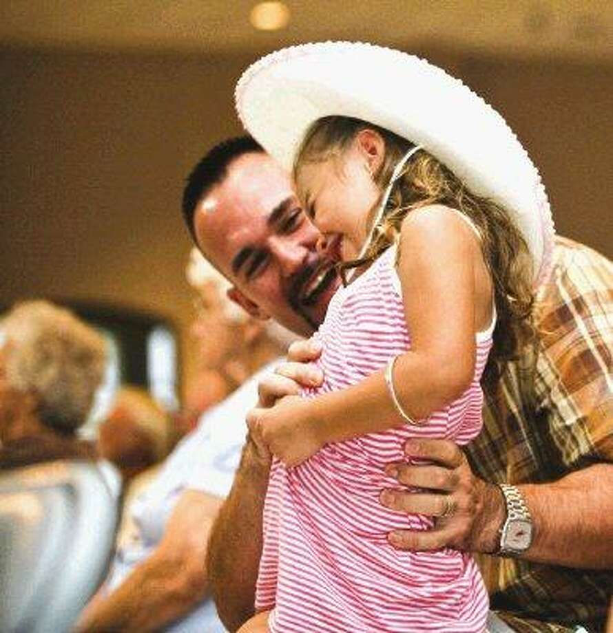 Brynn Baumer is tickled by her father during the Bay Area Bluegrass Association's monthly show in the Arolfo Civic Center. Open to the public, the shows feature championship musicians in a whirlwind of toe-tapping, finger clapping goodness. / 2010 Dan Wang