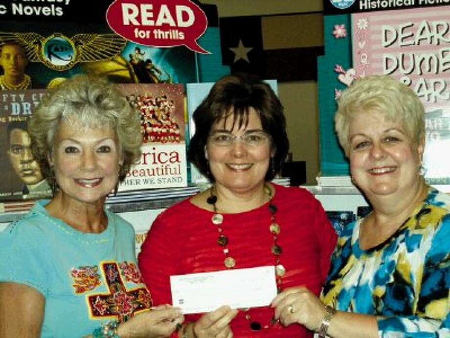 Ann Gibbins, Philanthropy Chair of the Kingwood Area Alumnae Chapter of Kappa Kappa Gamma, and Joan Hayes, Treasurer, present their $400 check to Jane Mehring (center), Librarian of Oaks Elementary School.