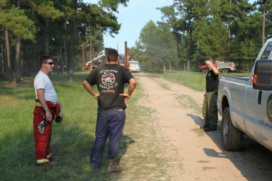 Tarkington firefighters Jason Ward and Logan Ward talk to a representative of the Texas Forest Service about a grass and woods fire at CR 2212 at CR 2232. The fire started on the morning of Wednesday, July 10, as a controlled burn, but by the afternoon it was out of control.