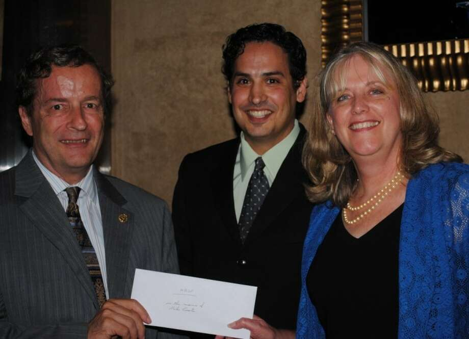 Rotary National Award for Space Achievement Foundation Treasurer Geoff Atwater, left, and President Rodolfo Gonzalez present NASA Aerospace Scholars Program Manager Linda Smith with a $32,700 donation for the Aerospace Scholars Program-- the proceeds from the 26th Annual Rotary Space Gala honoring Johnson Space Center Director Mike Coats in April. Photo: SUBMITTED PHOTO
