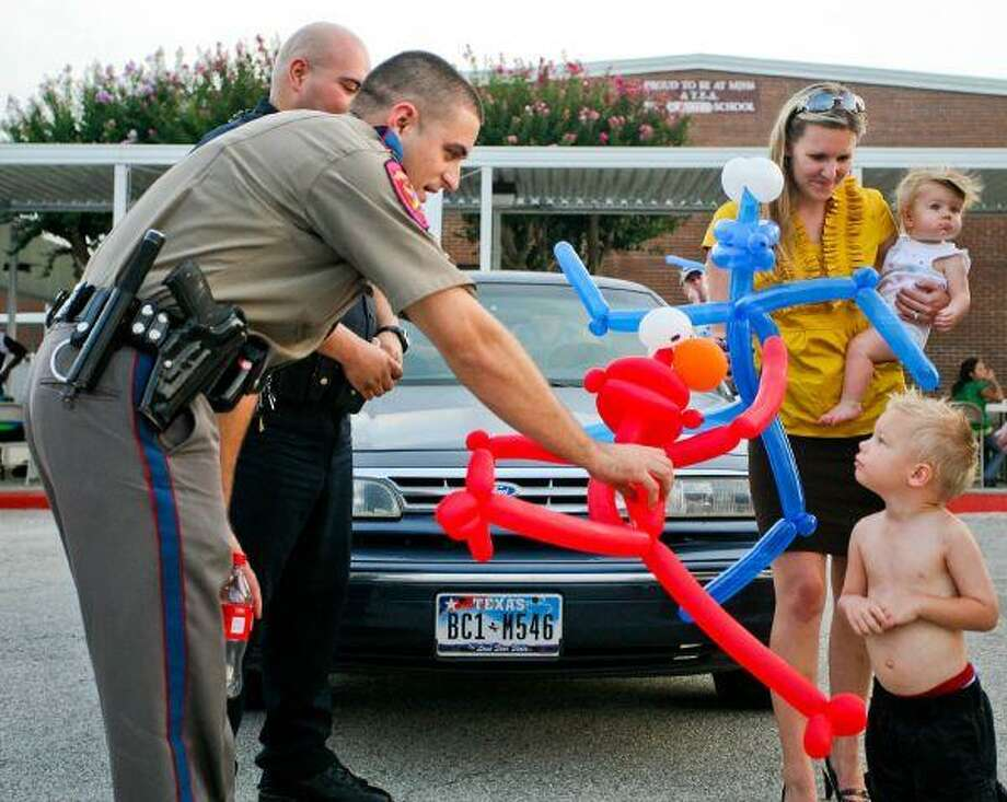 Noah Nicholas, 3, is offered an Elmo balloon animal from a Texas Highway Patrolman at the Magnoila National Night Out in the Sixth Grade Campus parking lot Monday evening. The event also included a water slide and live canine unit demonstrations. Nicholas ended up sticking with the blue Grover balloon animal. / 2010 Dan Wang