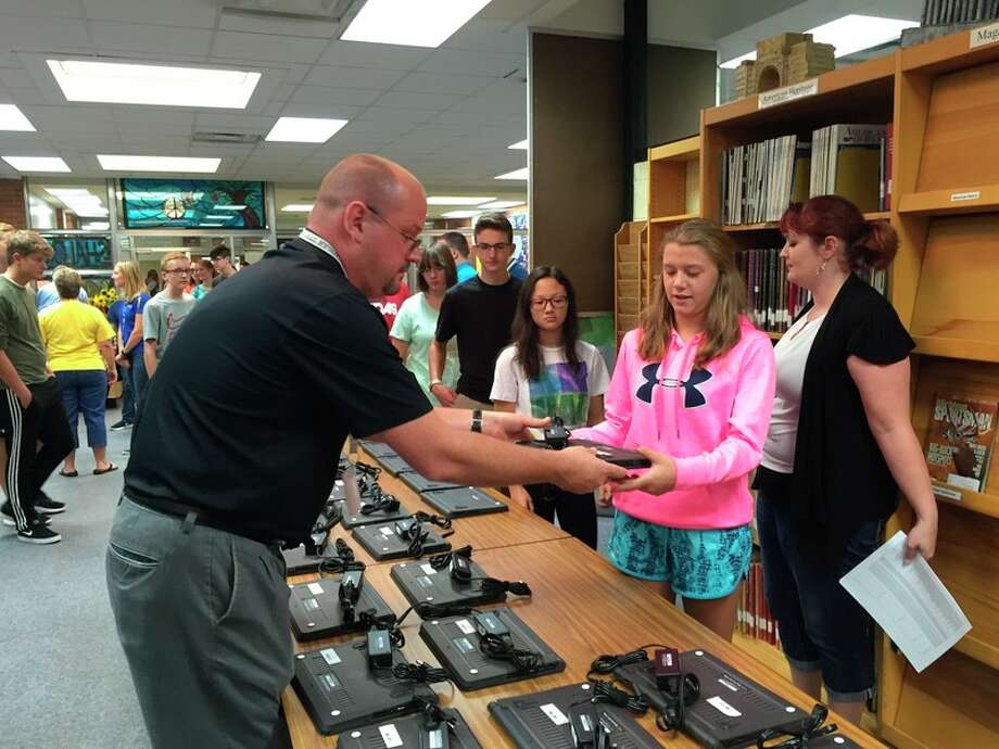 Midland Public Schools Director of Technology David Dziedzic, left, hands out a Chromebook laptop computer to a Midland High School student as MHS drama/English teacher Megan Applegate, right, looks on.
