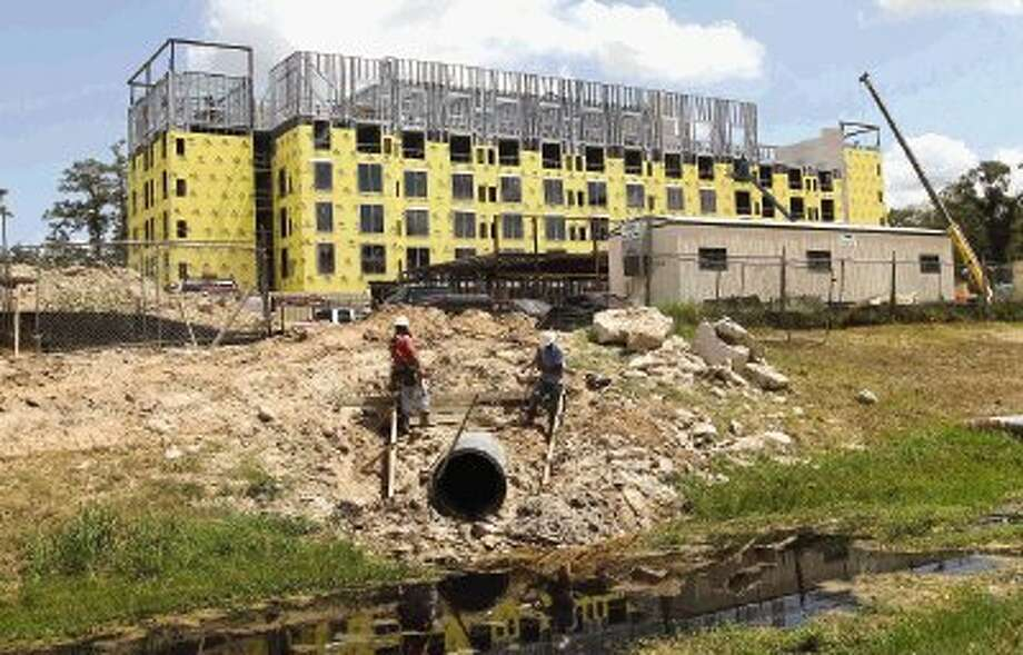 Construction workers dig around a pipe at a new Hyatt Place hotel site off Research Forest Drive and Grogans Mill in The Woodlands. As ExxonMobil and other companies prepare to move to the area, the local hotel industry expects an increase in hotel demand from business travelers. / Conroe Courier