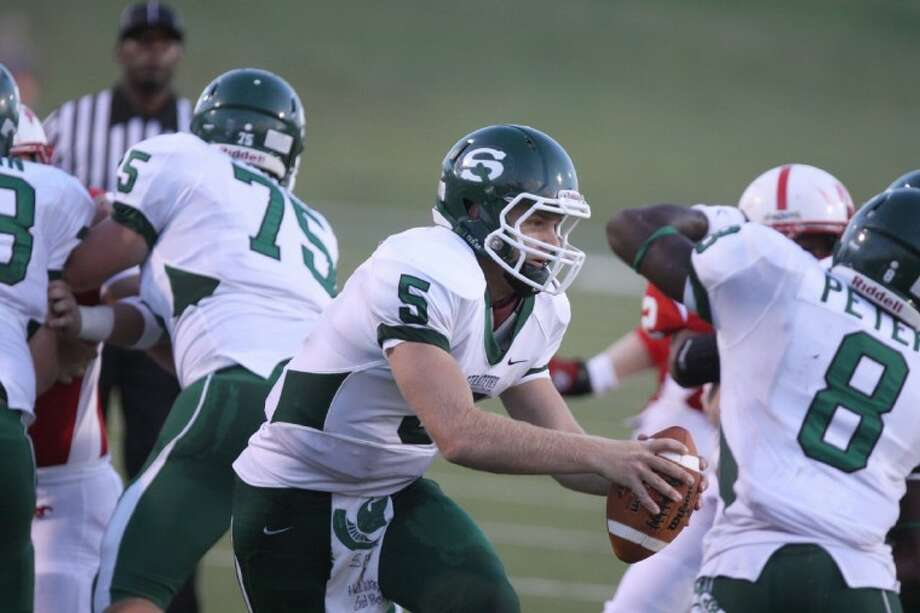 Stratford's Travis Hanes fakes a handoff against Memorial during the Spartans' season opening game at Tully Stadium. Hanes,. shown here getting a nice block from his offensive line and tailback Terrence Peters, threw a touchdown pass last Friday night to help Stratford beat Magnolia West, 17-7. Photo: Photo By Alan Warren