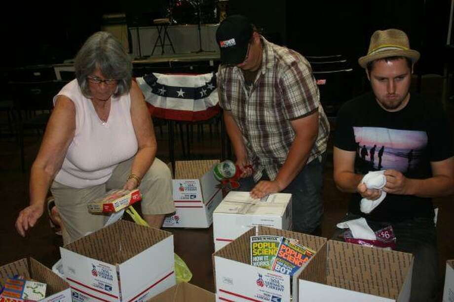 Becky Comstock, left, Caleb Pace, center, and Lincoln Lankford, right, help stuff care packages for the soldiers in Afghanistan to show their support and gratitude.