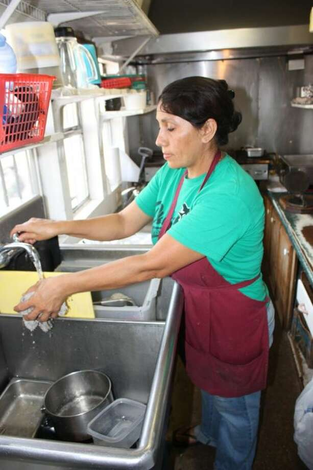 Ernestina Gomez, 48, cleans up after a long day of cooking and selling made-to-order tacos, gorditas, tortas, tostadas, burritos and quesadillas at Taqueria La Rancherita in Cleveland. Photo: RACHEL HALL