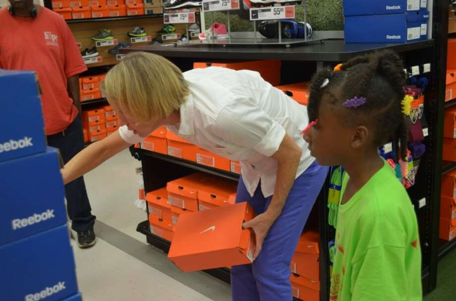 Trees of Hope guild member Margaret Pierce assists a young girl in finding shoes. The Trees of Hope organization recently had a Back to School event for the children of at Star of Hope. Photo: Submitted Photo