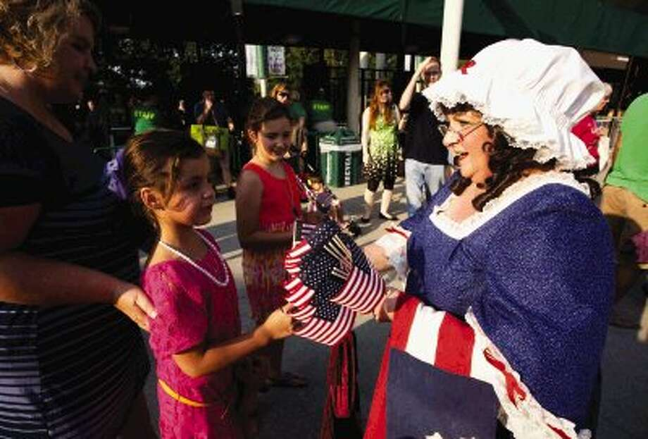 A woman dressed as Betsy Ross distributes free flags to concert goers during Wednesday's annual Star Spangled Salute with the Houston Symphony at The Cynthia Woods Mitchell Pavilion in The Woodlands. To view or order this photo and others like it, visit HCNPics.com. Photo: Staff Photo By Eric Swist