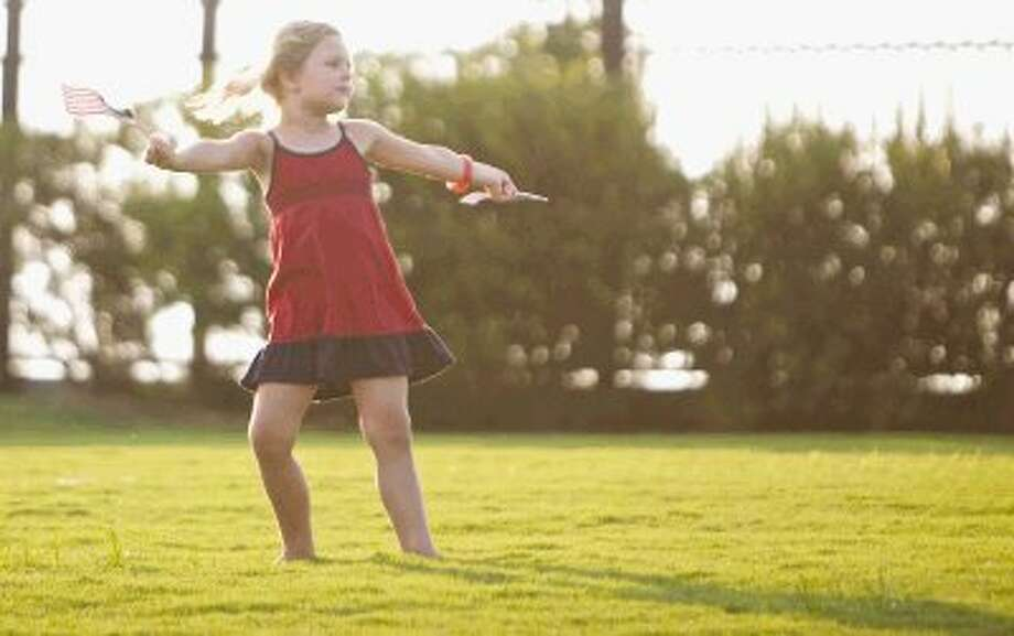 Mia Selever, 4, of The Woodlands, dances with American flags on the lawn before the start of Wednesday's annual Star Spangled Salute with the Houston Symphony at The Cynthia Woods Mitchell Pavilion in The Woodlands. To view or order this photo and others like it, visit HCNPics.com. Photo: Staff Photo By Eric Swist
