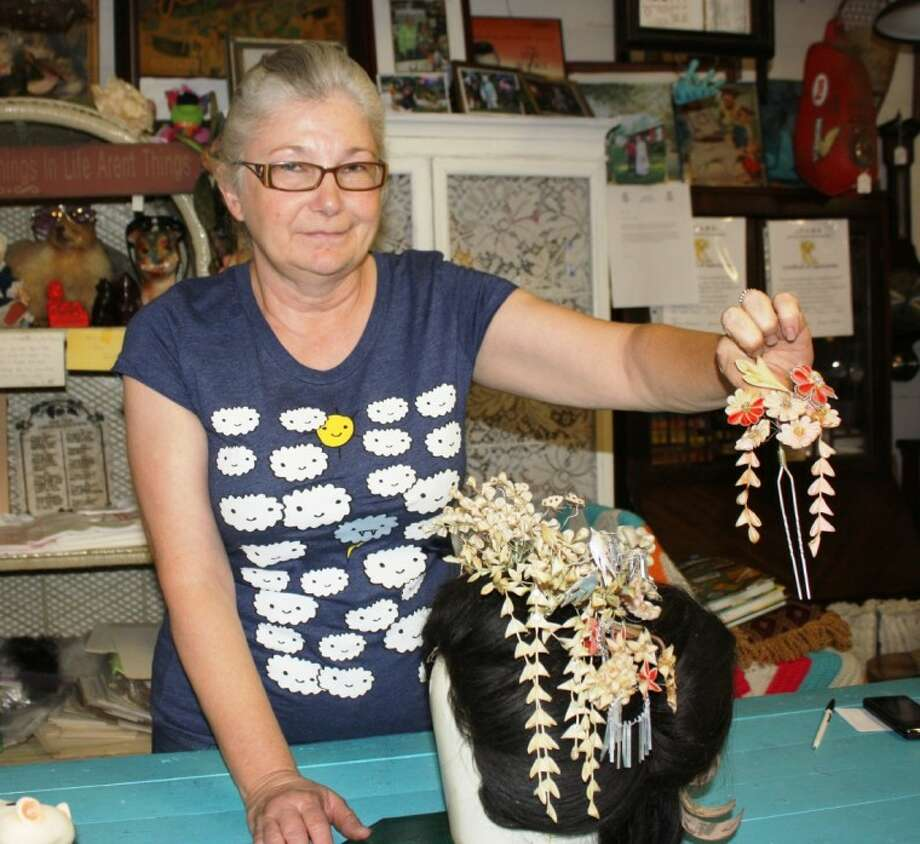 Earlene Herron displays one of the most unusual items in her shop Daisy Mae Sale & Resale. It is an authentic Geisha wig with hand-made silk and paper hair pins. The wig is made of real human hair and is from the 1930s. She purchased the item years ago at a yard sale. Photo: MELECIO FRANCO