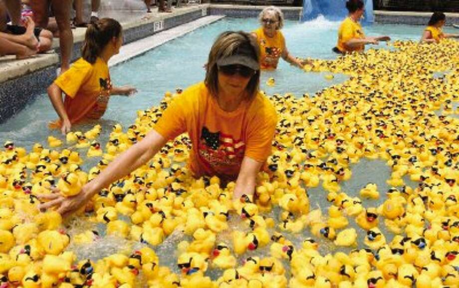 A volunteer pushes rubber ducks during Montgomery County Emergency Assistance's annual Great American Duck Race. More than 5,000 ducks floated around the pool at the Rob Fleming Aquatic Center in Creekside Park on Thursday. The event raised money for MCEA. Go to HCNPics.com to view and purchase this photo and others like it. / Conroe Courier