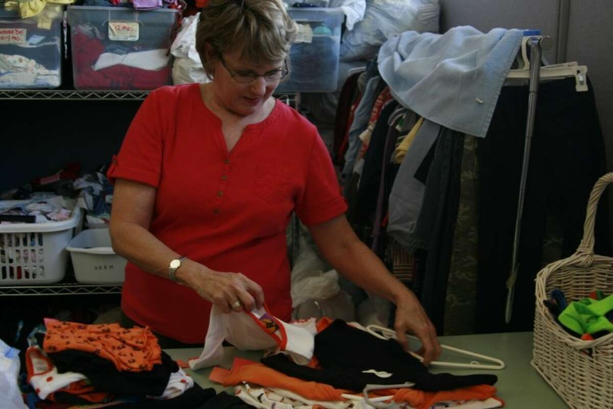Linda Hernandez, a volunteer with the Kingwood Women's Club, sorts baby clothing to hang in the HAAM Resale shop in Humble.