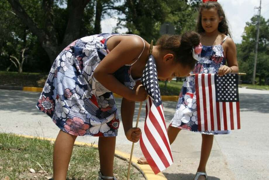 Jena and Kinley Robinson with their grandmother, Arliss Bentley, worked together to place several flags along Higgins St. in celebration of the Fourth of July.
