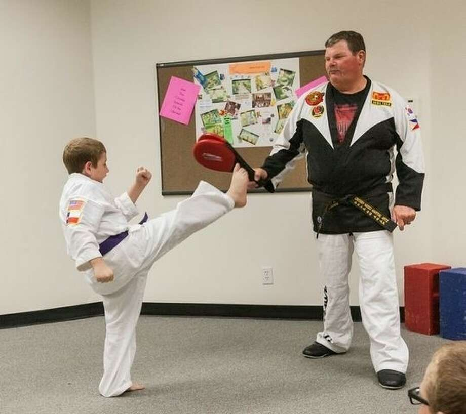Crosby Mixed Martial Arts Chief Instructor Randall Butler, right, calls on Wyatt Mills to demonstrate a front snap kick during the martial arts demonstration at the Crosby Branch Library on June 25. Photo: Word Photography