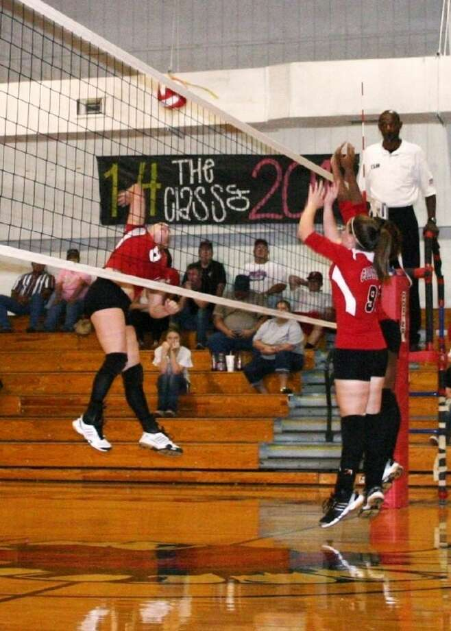 Airborne Angie Byers of the Cleveland Lady Indians, left, goes for the kill against a pair of Coldspring Lady Trojans who don't think so in high school volleyball action Sept. 14. Cleveland prevailed in three games. Photo: STEPHEN THOMAS