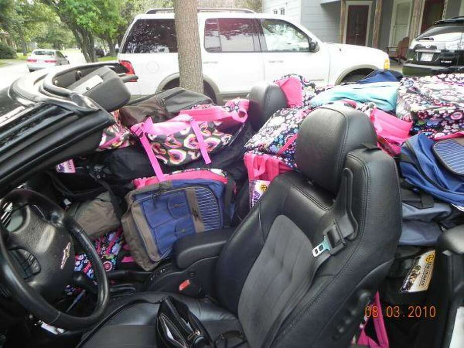 Delivery of the 150 backpacks filled by members of Rotary Club of West U for YMCA Operation Backpack took two vehicles.