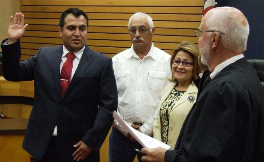 New District E Councilmember Cody Ray Wheeler takes the oath of office from Judge Les Rorick in the Council Chambers Tuesday (July 2) while Wheeler's parents (center) look on. Photo: JEFF NEWPHER