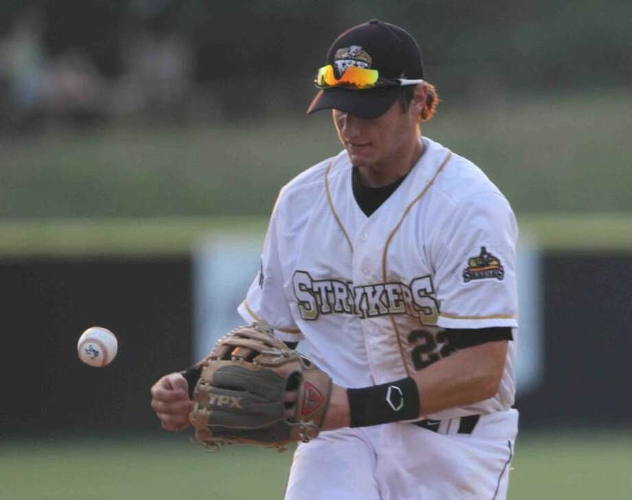 Strykers third baseman Dalton Perry drops the ball as he prepares to throw during a baseball game at The Woodlands Christian Academy Friday.