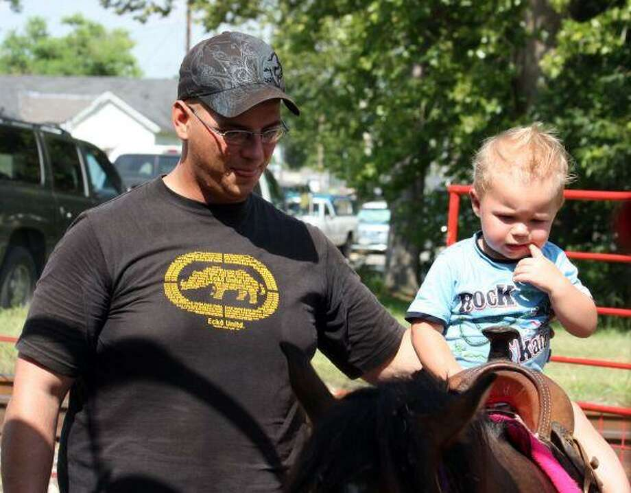 Matthew Danielson helps his 2-year-old son Nathan ride the pony Saturday at the petting zoo at the Hempstead Watermelon Music Festival. The Army specialist and his wife Sara brought Nathan from Fort Hood to enjoy the festivities.