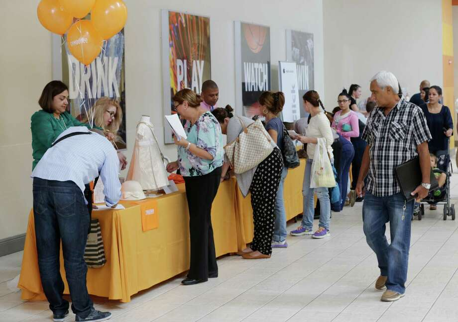 Job applicants fill out forms during a job fair in Miami. The Labor Department said weekly applications for jobless aid rose 3,000 to a seasonally adjusted 254,000. But the four-week average, a less volatile measure, ticked down to 256,000, matching a 43-year low first reached in April. Photo: Associated Press /File Photo / Copyright 2016 The Associated Press. All rights reserved. This material may not be published, broadcast, rewritten or redistribu