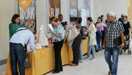 Job applicants fill out forms during a job fair in Miami. The Labor Department said weekly applications for jobless aid rose 3,000 to a seasonally adjusted 254,000. But the four-week average, a less volatile measure, ticked down to 256,000, matching a 43-year low first reached in April.
