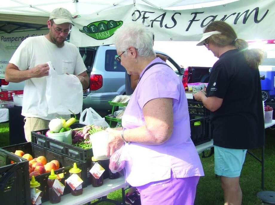 Tomball Farmers Market customers select fresh produce during a recent Saturday market. The Tomball Farmers Market is open every Saturday from 9 a.m. to 1 p.m. at the corner of Main and Cherry Streets in Tomball. Photo: Lindsey Vaculin