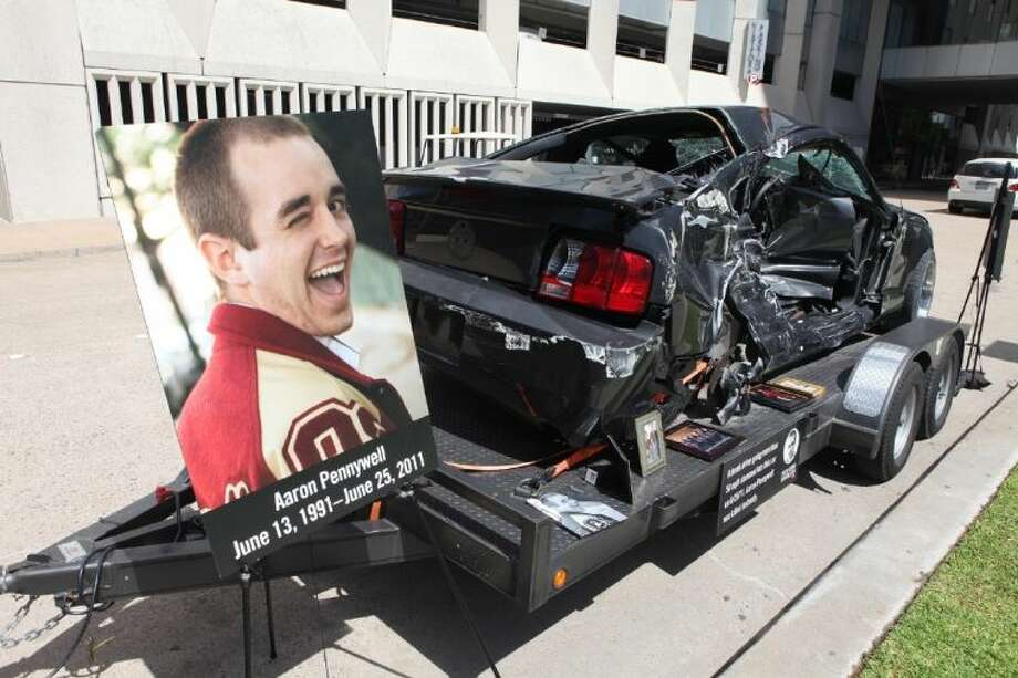 A poster of Aaron Pennywell sits next to his damaged car at the Faces of Drunk Driving launch event at the Gerald Hines Waterwall Park in Houston, Texas. Pennywell was killed by a drunk driver who ran a stop light and struck his vehicle on June 25, 2011.