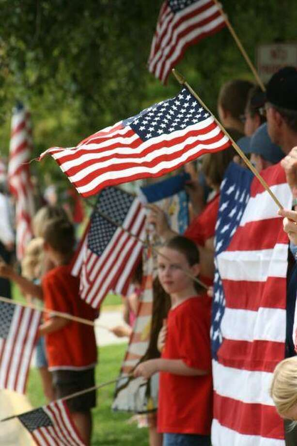 A group of well-wishers hold American flags to pay tribute to Dayton's hometown soldier, Jesse Ainsworth. Ainsworth, son of Margie and Gene Hutchins of Dayton, was killed July 10, 2010 in Afghanistan. It was the five-year soldier's third tour of duty.